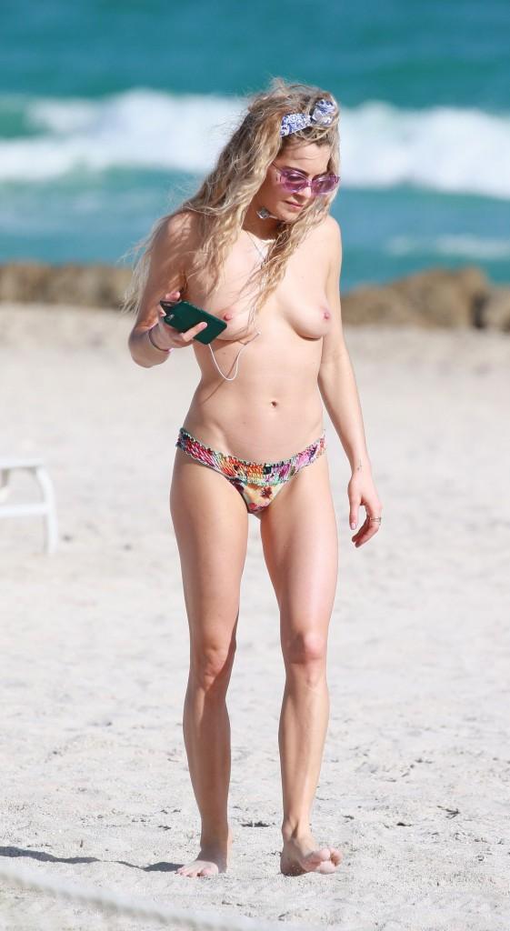 Chelsea Leyland walks topless on the beach in Miami Beach